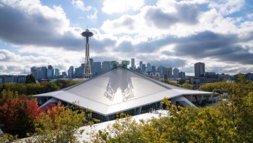 The exterior of Climate Pledge Arena on a partly cloudy day with the Space Needle in the background.