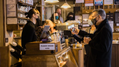 Dow Constantine and Jenny Durkan wear masks as they pay for goods at Cafe Allegro in Seattle.