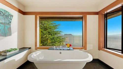 A white tub with windows that overlook the water.